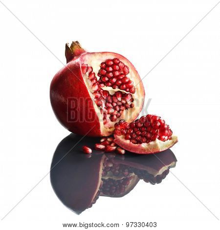 Pomegranate opened up on reflective white surface