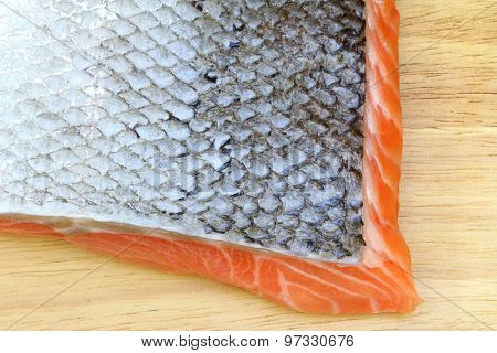 Closeup photo of Raw salmon with skin on wooden cutting board