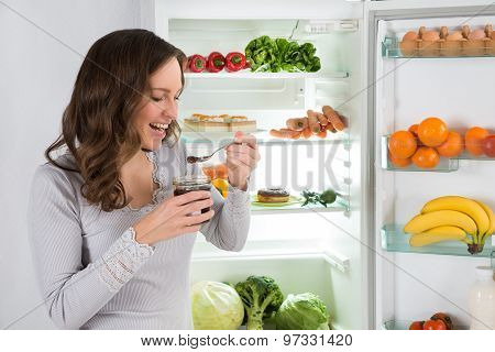 Woman Eating In Front Of Fridge