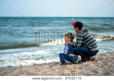 Two Brothers Sitting On Beach Against The Sea