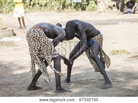BOR, SOUTH SUDAN-DECEMBER 4, 2010: Unidentified Dinka tribesmen wrestle in a small village north of Bor, South Sudan