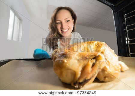 Woman Putting Chicken View From Inside The Oven