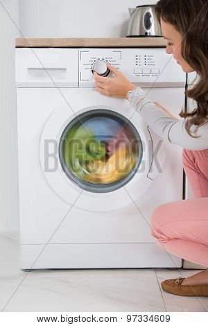 Woman Pressing Button Of Washing Machine
