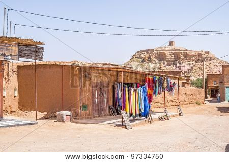 AIT BENHADDOU, MOROCCO - APRIL 10, 2015:  stands with souvenirs with historic town in background