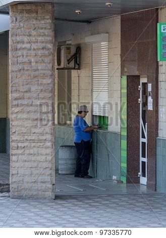 Makeevka, Ukraine - July 30, 2015: Elderly Woman Near An Atm At The Branch Of The Non-working Commer