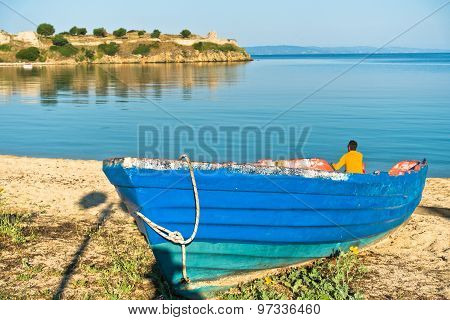 Blue boat on a sandy beach, old roman fortress in background