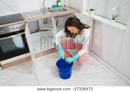 Woman Squeezing Wet Rag At Kitchen Room