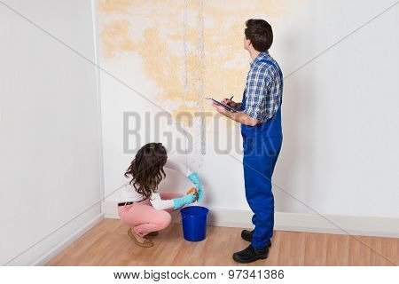 Worker Writing On Clipboard While Woman Squeezing Cloth
