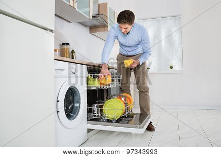 Man Putting Dishes In Dishwasher