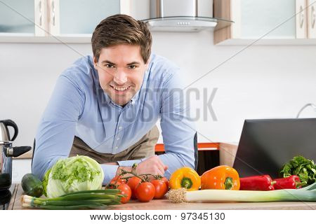 Man With Laptop And Vegetables In Kitchen