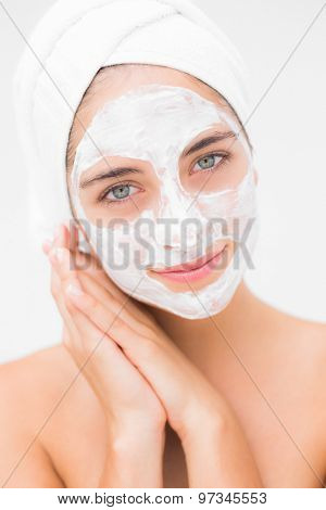 Portrait of an attractive woman having white cream on her face on a white background