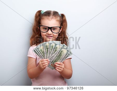 Happy Kid Girl In Glasses Holding Money In The Hand And Looking With Smile