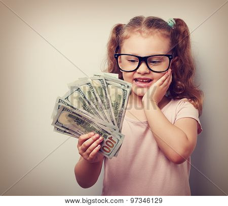 Surprising Emotional Kid Girl Holding Dollars In Hand And Thinking How Much Money She Have Earned. V
