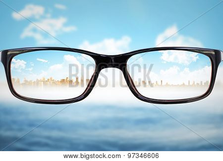 Glasses against cityscape on horizon over ocean