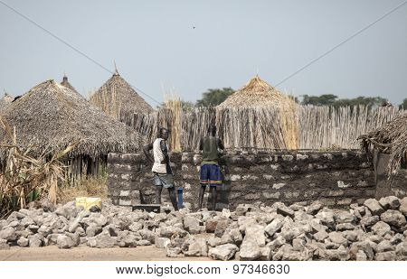 MANGALLA, SOUTH SUDAN-DECEMBER 2, 2010: Unidentified men build a new house out of stone in a remote area of South Sudan