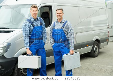 Worker With Toolbox Standing In Front Of Van