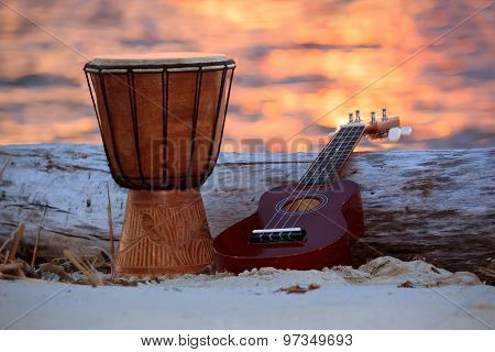 Ukulele and ethnic drum over a sunset beach.