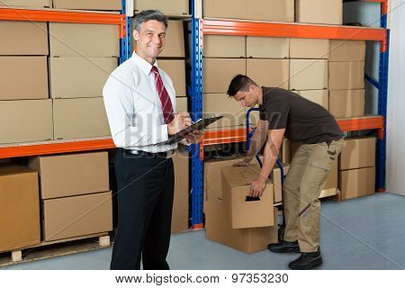 Manager With Clipboard And Worker In Warehouse