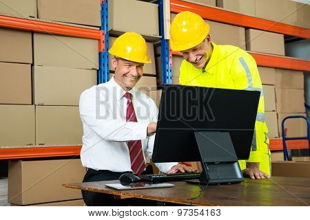Happy Warehouse Worker And Manager Using Computer
