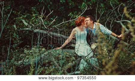 Happy Kissing Couple Is Sitting On The Branch Of Old Tree On The Woodland Background.
