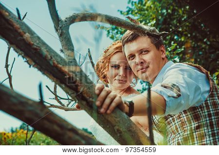 Happy Kissing Couple Is Sitting On The Branch Of Old Tree On The Rural Background.