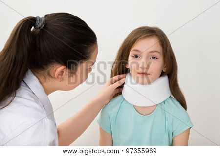 Doctor Examining Neck Of Patient