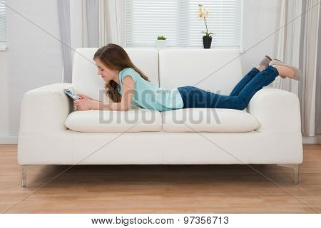 Girl On Sofa Looking At Digital Tablet