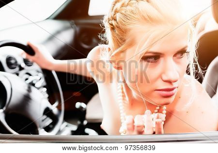 Young Woman In A Pearl Necklace Sat In The Drivers Seat Of Her Car