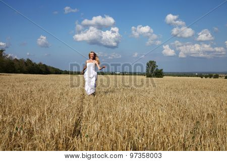 Full length portrait of a beautiful young happy woman in a white dress running through the wheat field