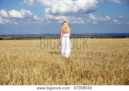 Full length portrait of a beautiful young woman in a white dress walking through the wheat field