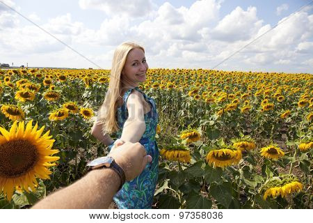 Follow Me. Close up portrait of a beautiful young girl in a blue dress on a background field of sunflowers