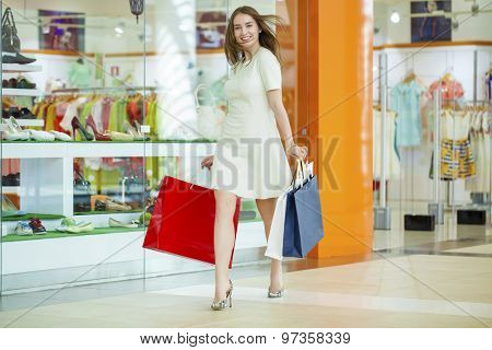Beautiful young woman in a white dress, holding shopping bags walking in the shop