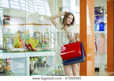 Portrait of a young beautiful woman on the background showcases a shoe store