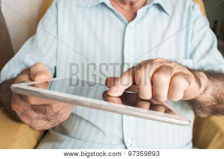 closeup of an old caucasian man sitting in an armchair uses a tablet computer