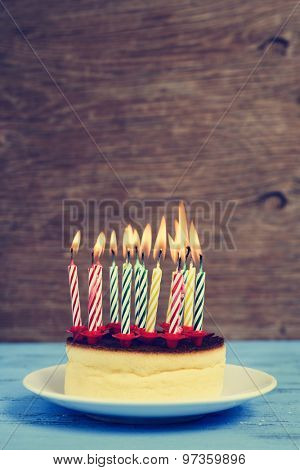 closeup of a cheesecake with some lighted birthday candles of different colors, with a retro effect