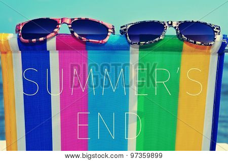 a pair of sunglasses on a colorful deck chair and the text summers end