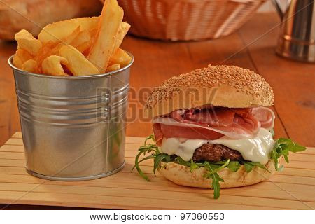 Prosciutto ham burger and fried potatoes.on rustic ambient.