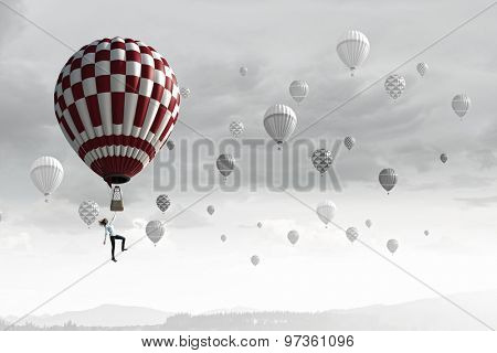 Businesswoman flying in search of ideas hanging on balloon
