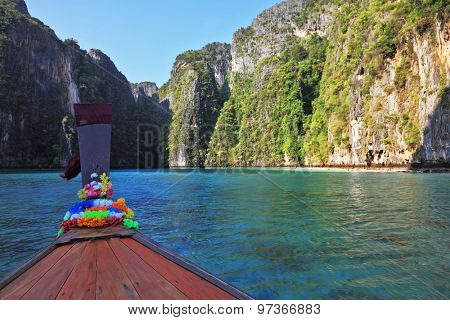 Thailand sightseeing boat sails in the picturesque bay. Bow is decorated with colorful and bright silk scarves