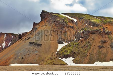 Rhyolite mountains. Colorful smooth mountains in the Icelandic reserve Landmannalaugar. In the hollows is last year's snow