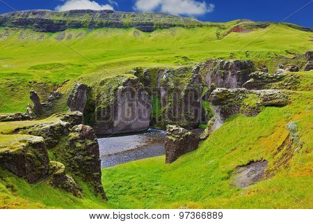 Picturesque rocks with yellowed grass around the canyon Fjadrargljufur. Neverland Iceland