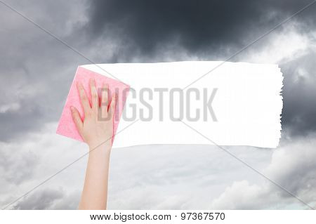 Hand Deletes Gray Clouds From Sky By Pink Rag
