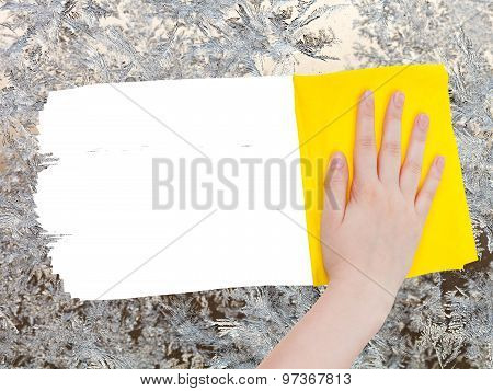 Hand Deletes Frozen Pattern On Glass By Yellow Rag