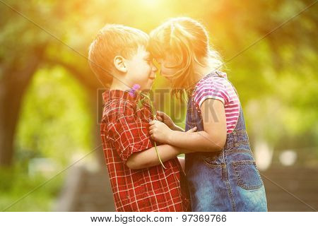 Happiness boy and girl with flower fun outdoor under sunlight
