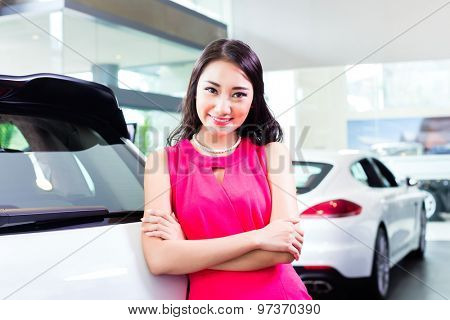 Asian Chinese woman buying SUV car marveling at the beauty of the auto