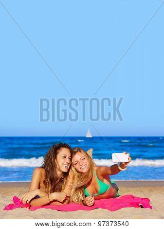 happy girl friends selfie portrait lying on beach sand in summer vacation