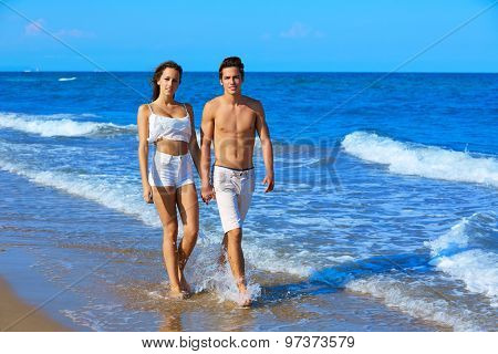 Couple young walking on the beach shore in summer vacation