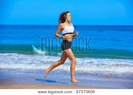 Beautiful brunette girl running in the beach at summer vacations