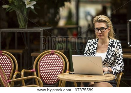 Young business woman at cafe with laptop looking at the camera.