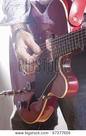 Music Concepts. Male Guitar Player Performing With Electric Guitar Hands Closeup. Mixed Light Used.